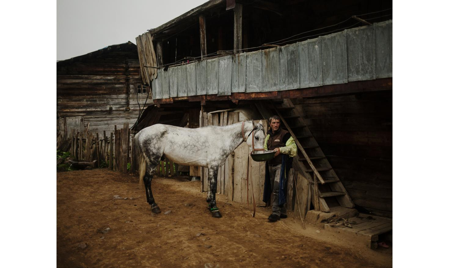 Zortikheli. A man feeds his horse. Horses are mainly used by men to accompany cattles in the pasture.