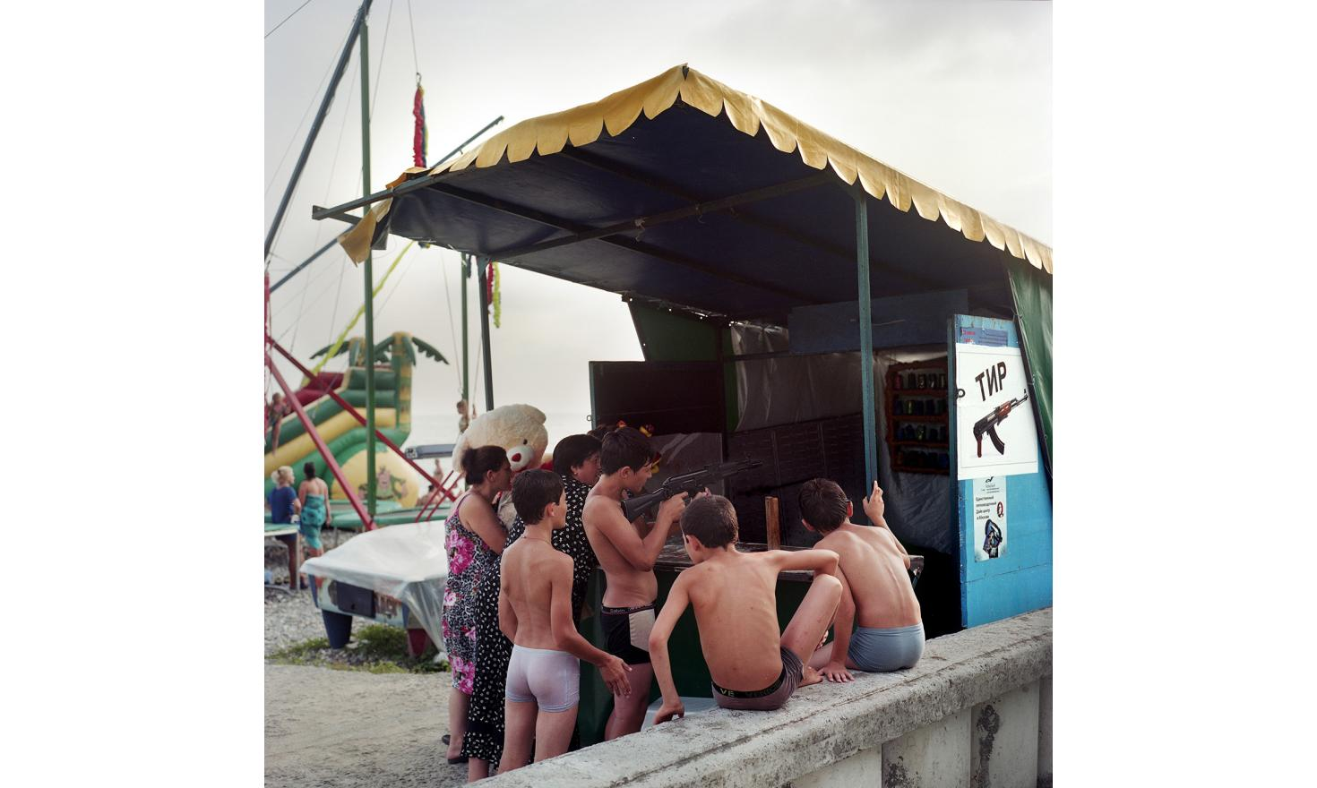 Kids playing at a shooting game on Sukhum(i) Beach.