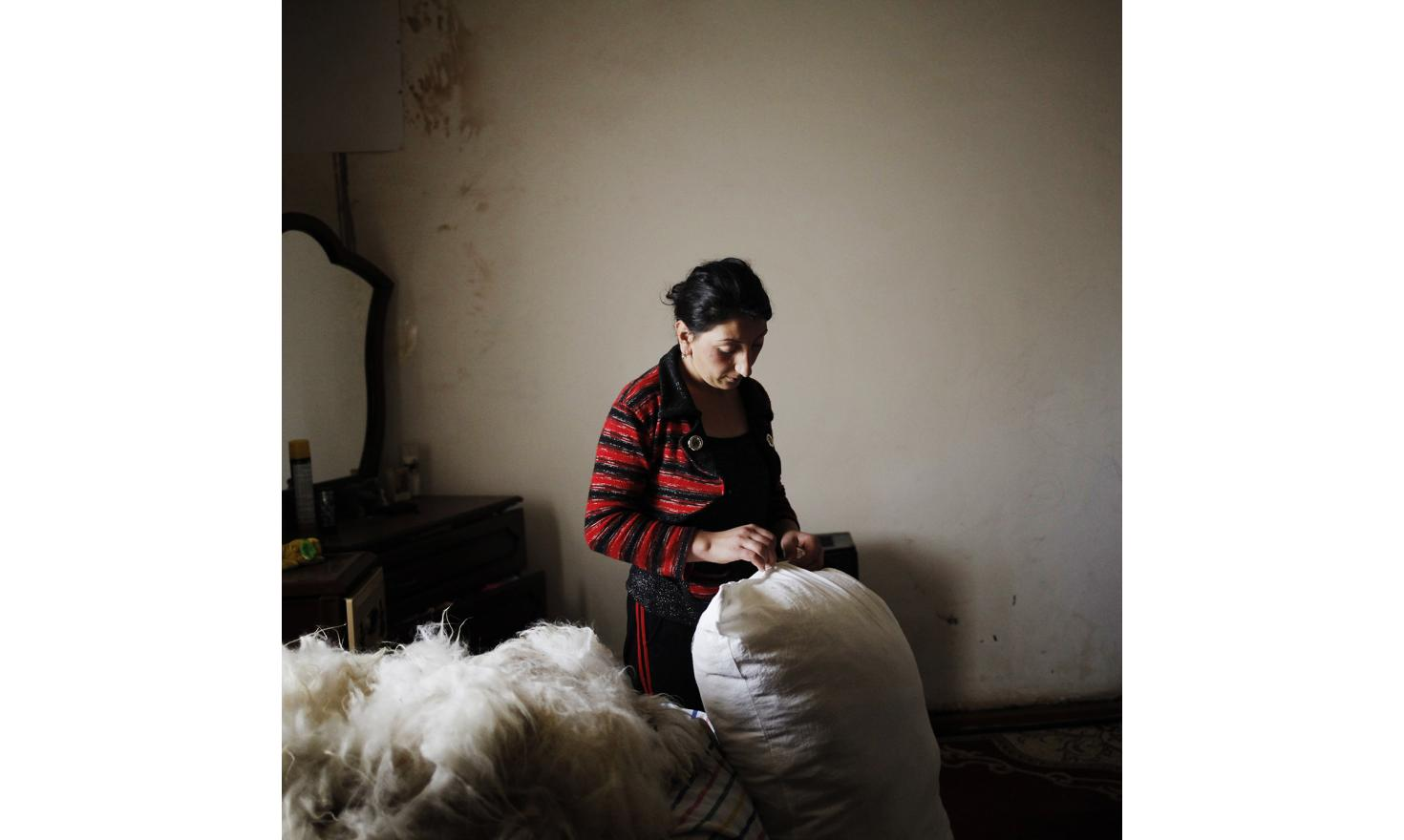 Early in the morning, Ruzanna prepares bed mattress for her children with sheep wool bought a few days ago.