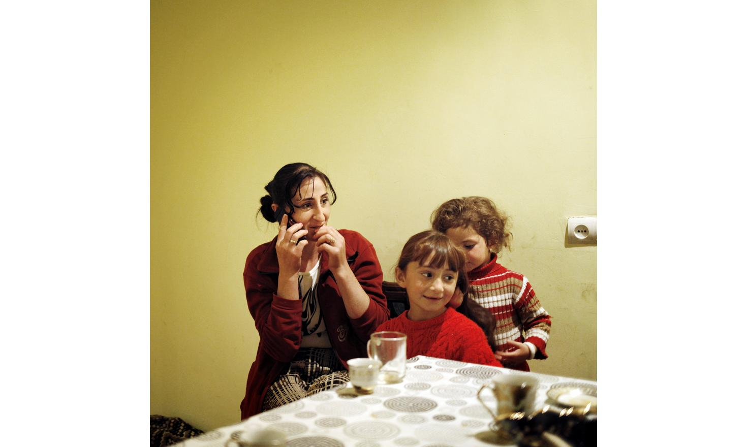 Anoush is calling her husband in Russia. On her the right are her two daughters, Lilith is doing Asmik's hair.