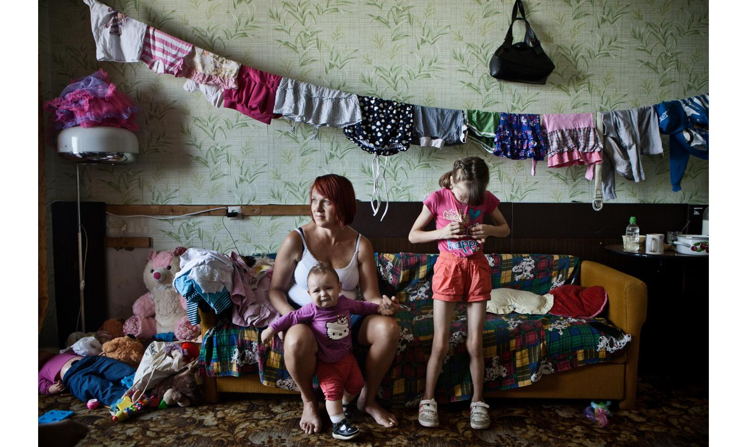 """Olia and Oleg, Valeria (9 years), Valentina (4 years), Timur (3 years), Miroslava (10 months).  Two days by train to come from Alchevsk, Luhansk region. """"We just managed to get three suitcases. One for each child [...]  Contact the agency for entire text"""