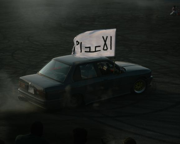 One of the contestants races on the track while displaying the name of his team on a flag: the Executioners