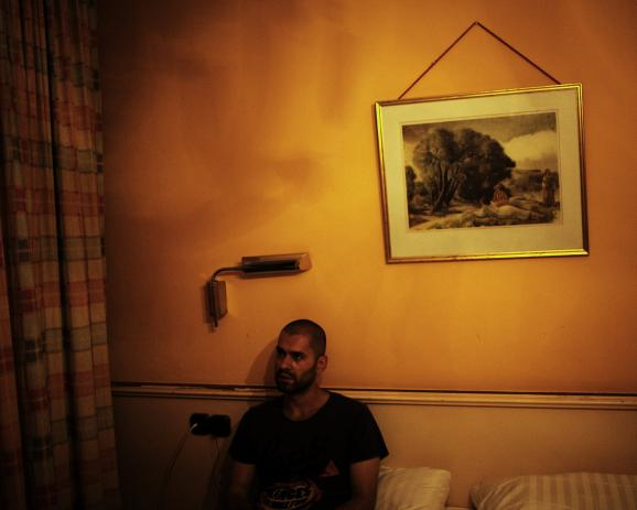 """M. A. Munich, Germany. July 2014 """"If it work, maybe it will be the end of suffering."""" M. A. M. A. left Aleppo six month ago, where his parents remain. He is travelling in fear of identity control. In this crappy hotel, the owner don't mind illegal..."""